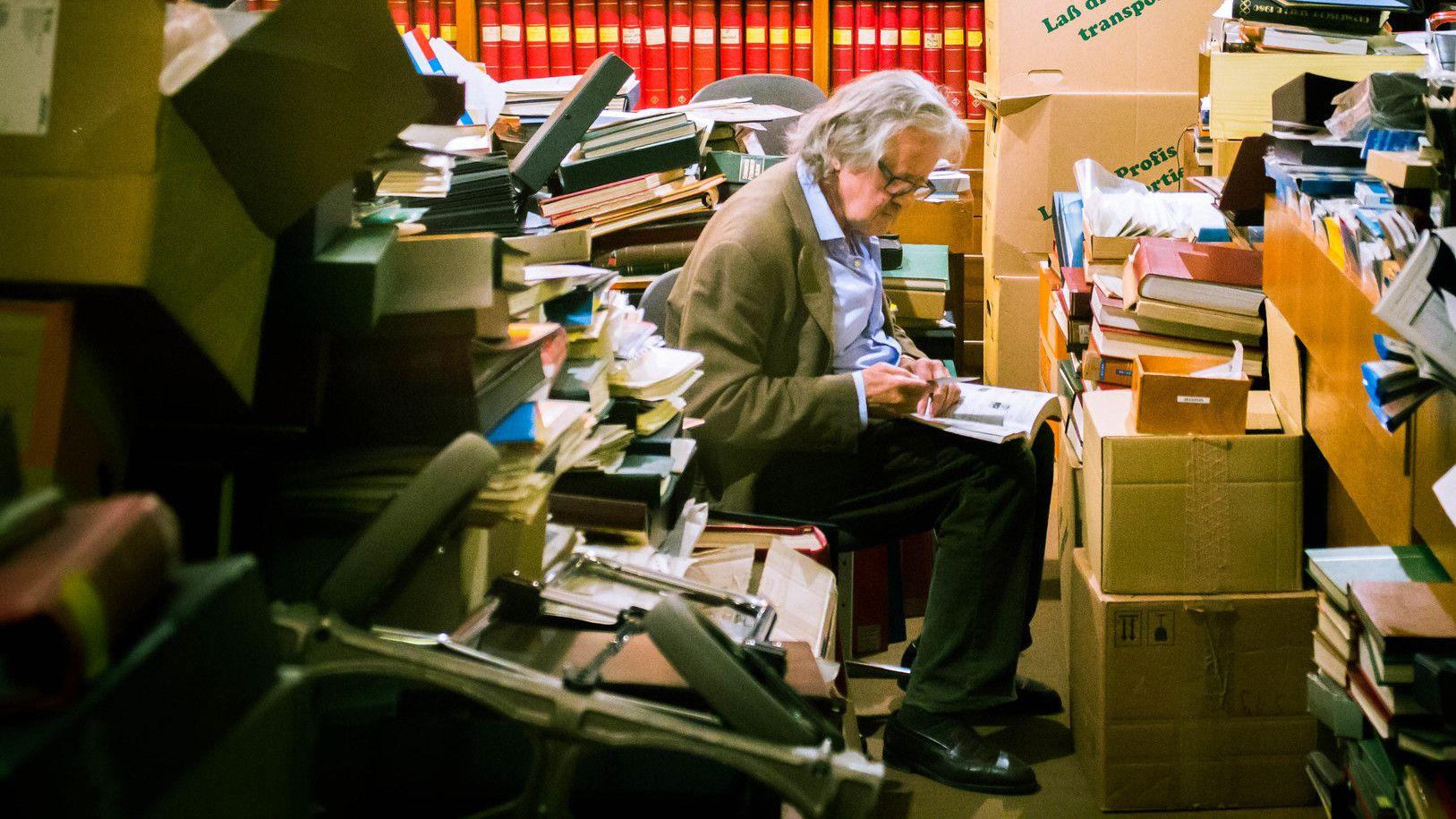 Un homme aux cheveux blancs assis parmi un chaos de documents, écrivant sur un bloc-note.