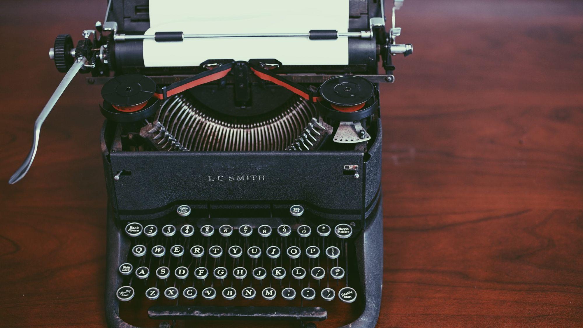 Une ancienne machine à écrire LC Smith, chargée avec une page vierge.