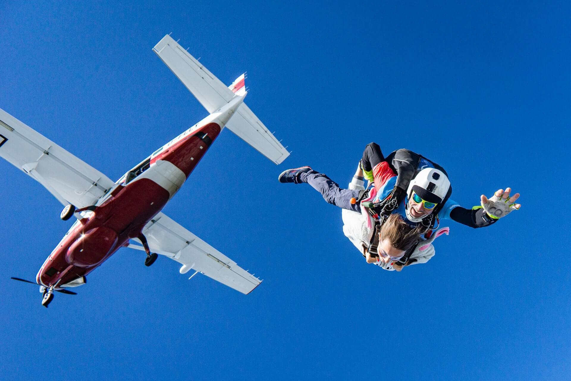 Photographie en contre-plongée d'un ou d'une parachutiste sautant d'un avion rouge, attachée en duo avec son moniteur